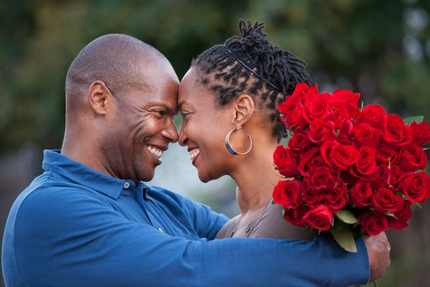 Man-hugging-wife-and-giving-her-red-roses